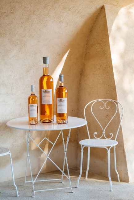 small medium and big pink wine bottles with white cap of le pétale de rose, organic rosé wine on a white table with white chair of barbeyrolles vineyard, france