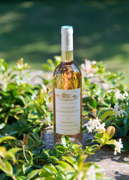 a pink rose wine bottle with white flower and green plant organic rosé wine of barbeyrolles vineyard, france
